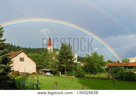 Double rainbow over a church in a cloudy village. Traditional farm with church in a village and double rainbow over woods and trees