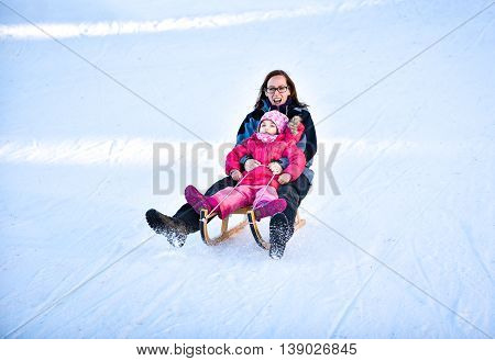Mother and little child are sledging very fast in ski mountain resort. High speed braking. Active family vacation on snow in the nature.