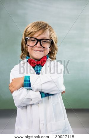 Portrait of smiling boy dressed as scientist standing in classroom
