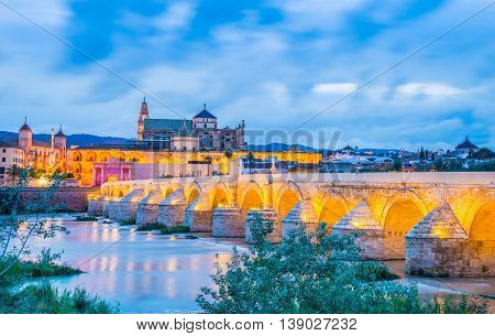 Night panorama over the roman illuminated bridge in Cordoba - Andalusia, Spain