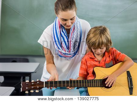 Young teacher assisting boy to play guitar in classroom