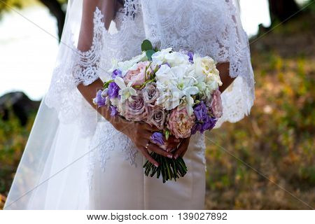 Graceful bride's hands with a nice bouquet