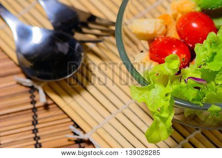 Fresh green salad with spoon and fork