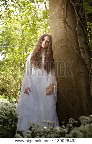 Beautiful woman wearing a long white dress leaning against a tree looking straight to camera