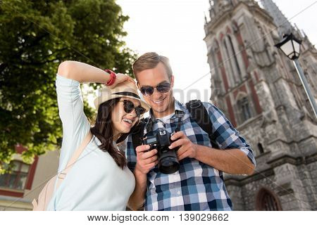 Enjoyable day. Positive smiling content tourists using photo camera and expressing joy while having a walk