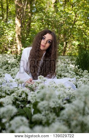 Beautiful woman wearing a white sitting in a forest surrounded by a sea of white flowers