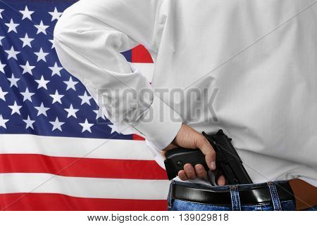 Man with gun tucked in pants on star and stripes background