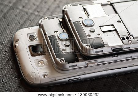 Stacked disassembled cell phones on table selective focus