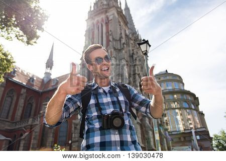 Live fully. Cheerful handsome man thumbing up and expressing joy while having a walk in the city