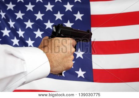 Man's hand holding gun on star and stripes background