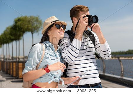 Remember it. Cheerful delighted couple taking photos and having a walk while feeling content