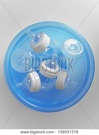 Baby bottles in plastic blue basin