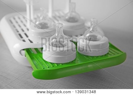 Baby bottles on plastic drying rack on wooden surface