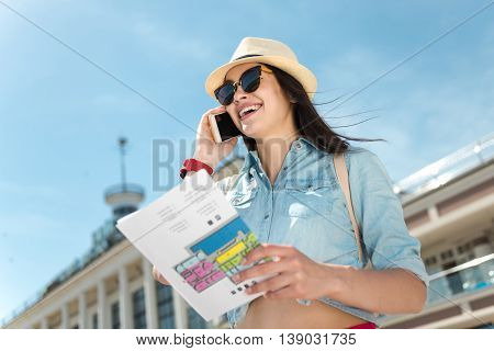 Pleasant call. Cheerful delighted beautiful woman smiling and talking on cell phone while holding city map