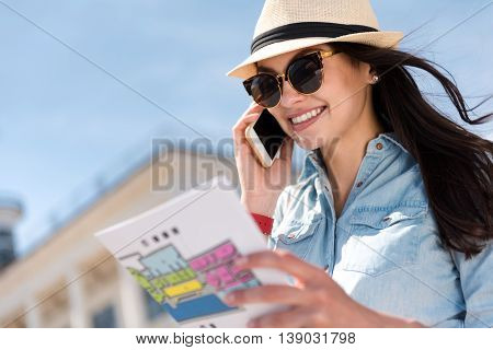 Get in touch. Pleasant cheerful delighted woman holding city map and talking on cell phone while feeling joyful