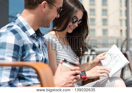 Just look. Positive smiling couple sitting on the bench and looking at the city map while resting