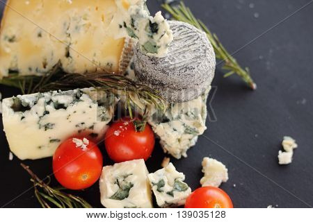 Roquefort cheese composition on dark background closeup