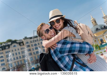 My beloved. Cheerful delighted smiling couple embracing and standing near fountain while having a walk