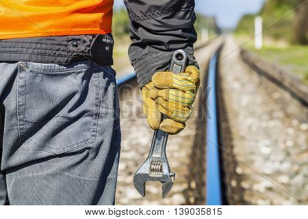 Railroad worker with adjustable wrench on railway in spring
