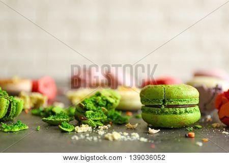 Green broken tasty macaroons on gray table