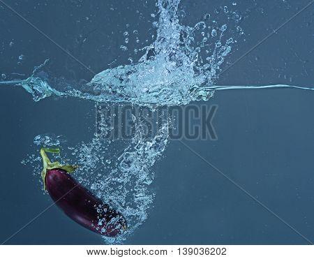 Fresh eggplant falling in water on dark background
