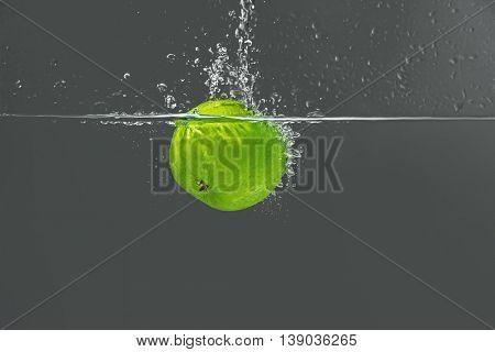 Fresh green apple falling in water on dark background