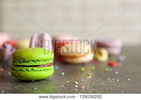 Green tasty macaroon on gray table