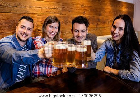 Portrait of happy friends toasting beer at restaurant