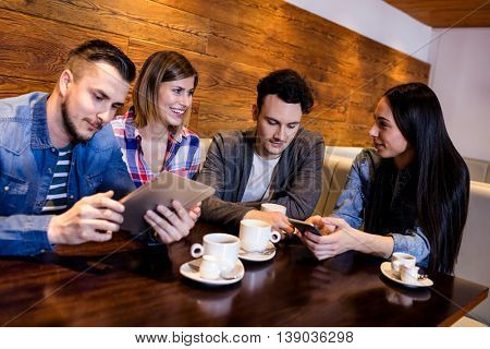 Friends using digital tablet and mobile phone while sitting at restaurant