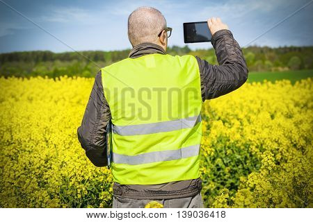 Farmer take pictures on tablet PC at rape field