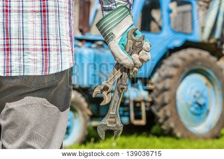 Worker with adjustable wrench near the tractor