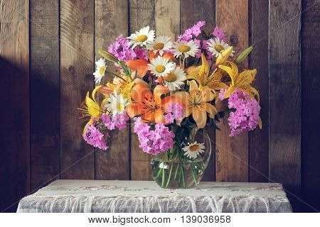 Still life with a bouquet of garden flowers in a glass jug against the wall. Rustic style.