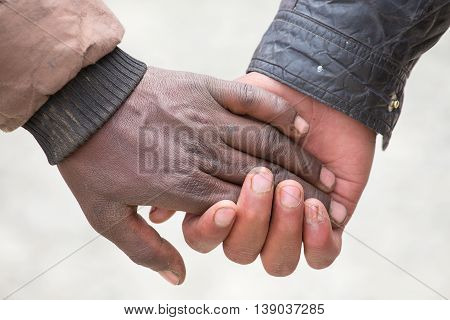 Couple hands on the street in India close up. In India it is normal to go to men holding each other by the hand