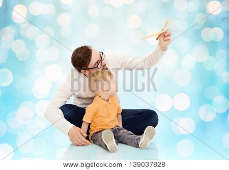 family, childhood, fatherhood, leisure and people concept - happy father and little son playing with toy airplane over blue holidays lights background