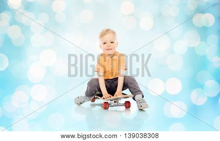 childhood, sport, leisure and people concept - happy little boy sitting on skateboard over blue holidays lights background