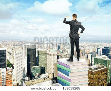 businessman standing on stack of book and looking to city view.