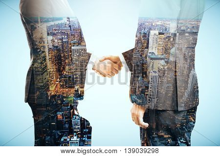Businessmen shaking hands on grey city background. Double exposure
