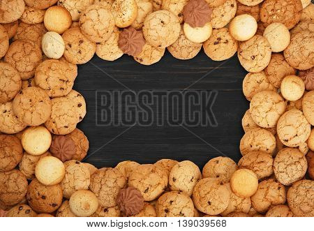 Cookies and sweet biscuits frame at black wood background with copy space. Oatmeal and chocolate drops cookies border. Dessert on wooden table top view