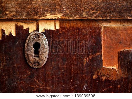 Rusty keyhole in old wooden table selective focus copy space