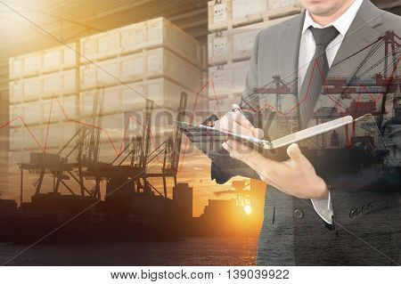 Businessman writing notebook with blurred cargo in wooden case and transportation port background trading export abroad concept