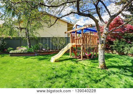View Of Kids Playground In Green Backyard Garden With Birch Trees And Flower Bed.