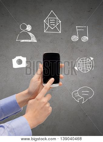 people, technology and communication - close up of hands with smartphone and media doodles over gray concrete background