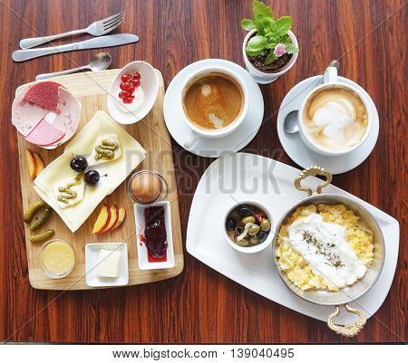 Breakfast table with cheese plate, olive, bread, fresh fruits and coffee