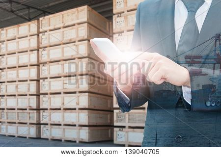Double Exposure Of Businessman Using Smart Phone And Transportation Port With Blurred Cargo Warehous