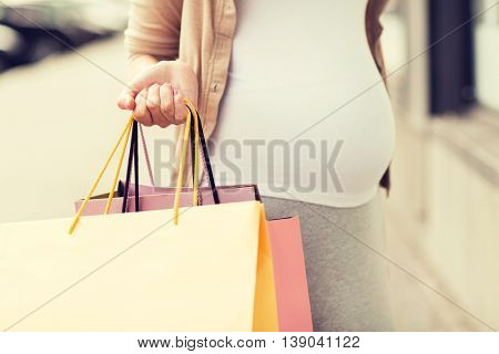 pregnancy, motherhood, people and expectation concept - close up of pregnant woman with shopping bags at city street