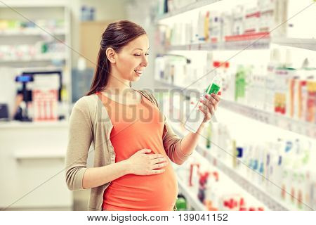 pregnancy, medicine, pharmaceutics, health care and people concept - happy pregnant woman choosing anti stretch marks lotion at pharmacy