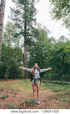 Young happy hiker woman with backpack raising her arms and enjoying the forest. Freedom and nature concept.