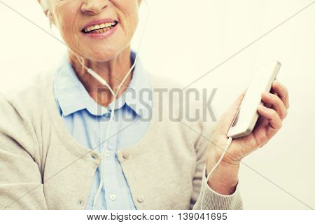 technology, age and people concept - close up of happy senior woman with smartphone and earphones listening to music at home