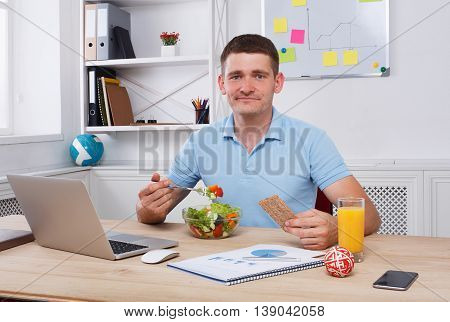 Man has healthy business lunch in modern office interior. Young handsome businessman at working place, looking at camera with vegetable salad in bowl, diet and eating right concept.