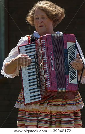 ROMANIA TIMISOARA - JULY 10 2016: Old woman singer at accordion from Poland in traditional costume present at the folk festival